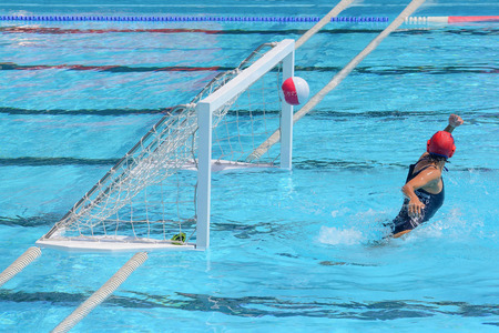 misses: A water polo goalkeeper misses the ball going into the net of the goal.