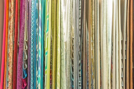 Colorful curtain samples hanging from hangers on a rail in a display in a retail store Archivio Fotografico