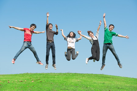 asian men: summer, holidays, vacation, happy people concept - group of friends jumping on the park Stock Photo