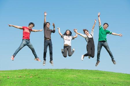 personas saltando: verano, vacaciones, vacaciones, feliz a la gente concepto - grupo de amigos que saltan en el parque Foto de archivo