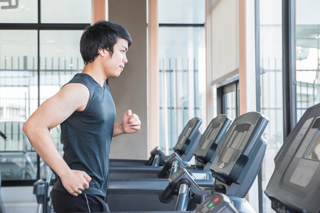 young man smiling: man at the gym doing exercise on the treadmill