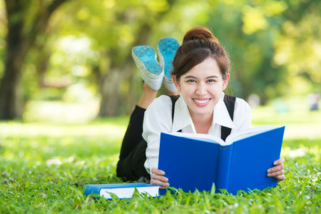Smiling casual student lying on grass reading book photo