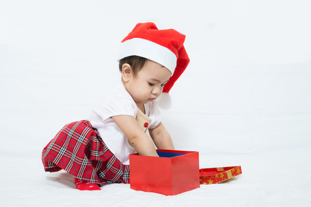 asian baby girl: Asian baby with christmas cap pick up something in gift box