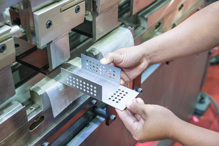 metal cutting: Worker at manufacture workshop operating cidan folding machine Stock Photo