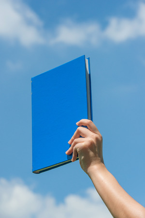 discipleship: Hand holding book over blue sky Stock Photo