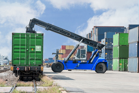 forklift handling container box loading to freight train photo