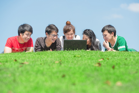 asia women: Group of students outdoors lying on grass and looking computer