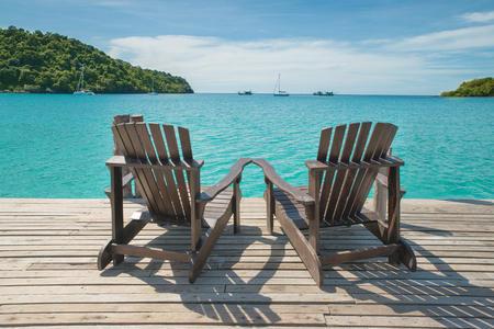 Two beach chairs placed on wooden floor at the sea view photo