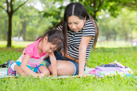 child studying: Little girl drawing with her mother laying on the grass Stock Photo