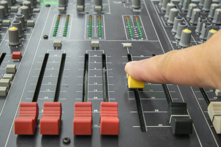 music production: Finger pushing a mixing desk slide. Selective focus