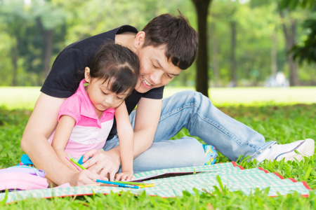 asia smile: Happy kid and dad paint together in park Stock Photo