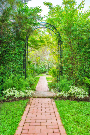 arbor: Lush green garden with wrought iron arbor