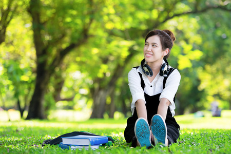 Female student girl outside in park listening to music on headphones while studying photo