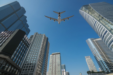 Shot of airplane flying above skyscrapers in City of Bangkok downtown photo