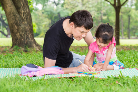 Happy kid and dad paint together in park Stock Photo
