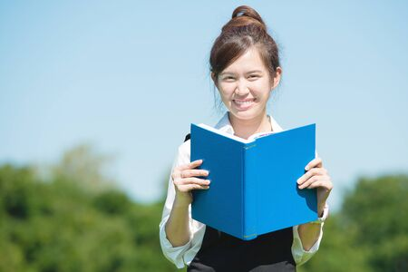 Asian student in the park with book and lecture note photo