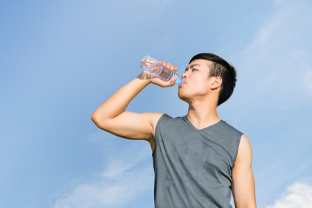 man drinking water: Thirsty athlete drinking water after workout