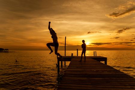 springboard: Siluetas de mujer salto en el mar desde el muelle