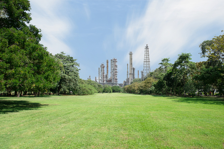 oil park: Beautiful green park with oil refinery and smokestack in background