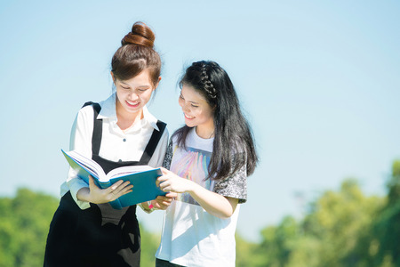 thai student: Two asian students reading a book in park