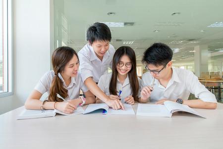 estudiantes: Grupo de estudiantes asi�ticos en el uniforme que estudian juntos en aula Foto de archivo