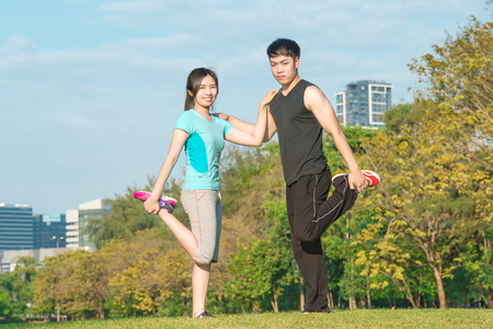 thai stretch: fitness, sport, training and lifestyle concept - Asian couple stretching outdoors