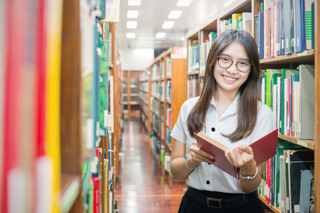 Asian student in uniform reading in the library at university photo