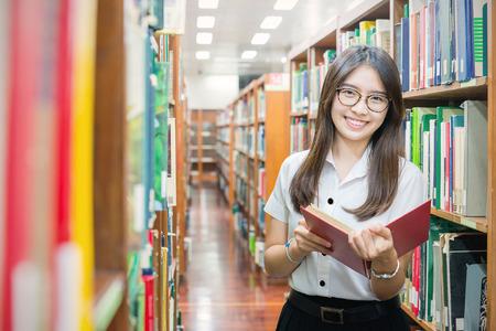 uniformes: El estudiante asi�tico en la lectura uniforme en la biblioteca de la universidad