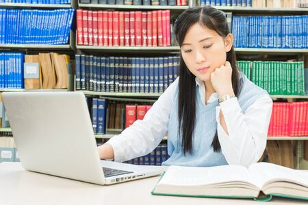 Asian student using laptop computer in college library photo