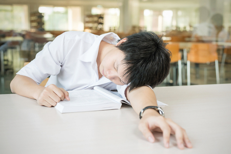 jaded: Asian student lying and sleeping on the school desk
