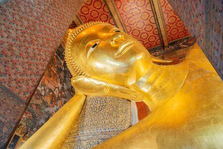 reclining: Reclining Buddha gold statue face. Wat Pho, Bangkok, Thailand