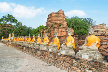 aligned: Aligned buddha statues with orange bands in Ayutthaya, Thailand Stock Photo
