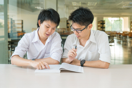 taught man: Two Asian students studying together at university Stock Photo