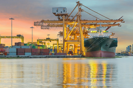 Industrial Container Cargo freight ship with working crane bridge in shipyard at dusk for Logistic Import Export background photo