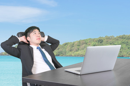 day dreaming: Businessman at office thinking and dreaming about summer vacation travel go to the sea in next holiday