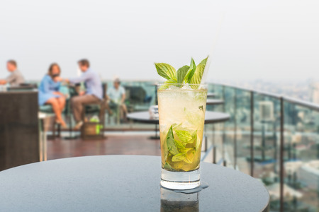 Mojito cocktail on table in rooftop bar photo