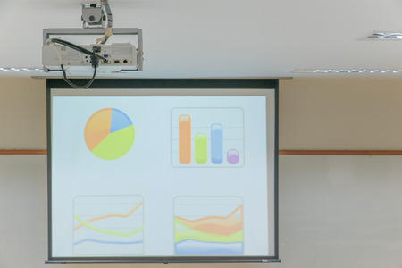 Projector hang on ceiling in Lecture room Stock Photo