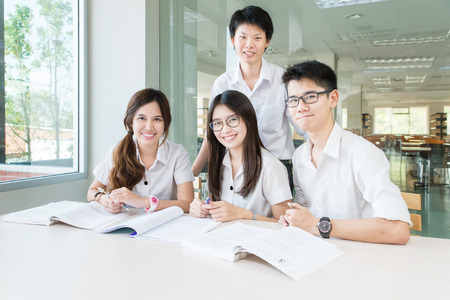 group study: Group of asian students in uniform studying together at classroom Stock Photo