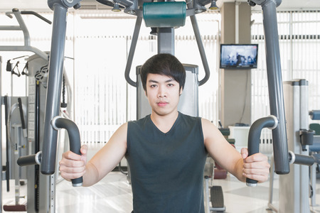 strong arm: Asian man having fitness training in gym to build up muscle on a weight machine Stock Photo