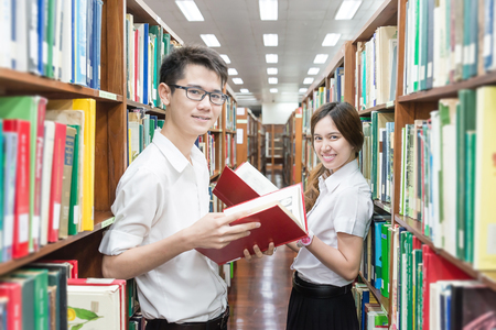 thai student: Asian couple of students in uniform at library