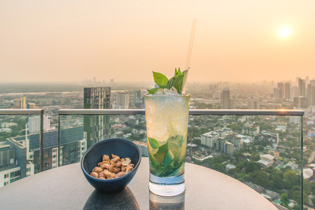 fruit bars: Mojito cocktail and cashews on table in rooftop bar