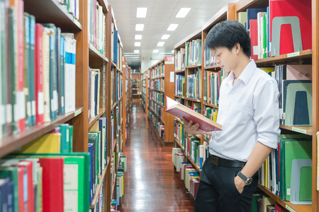 high school students: Asian student in uniform reading in the library at university