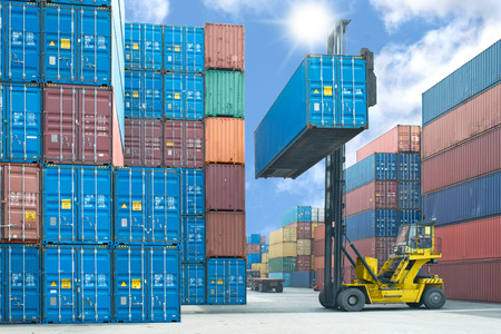 container port: forklift handling container box loading to truck in import export logistic zone