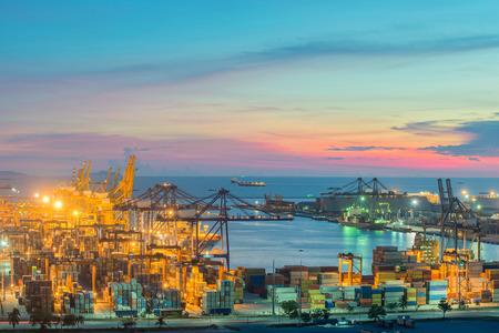 Behälter-Frachtfrachtschiff mit Kranbrücke in der Werft in der Abenddämmerung für Logistic Import Export arbeiten