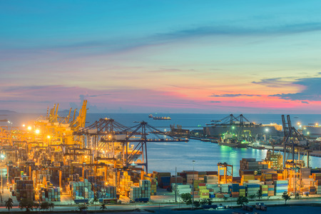global logistics: Container Cargo freight ship with working crane bridge in shipyard at dusk for Logistic Import Export