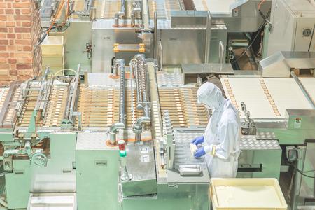 Trabajador que trabaja con la máquina en la fábrica de galletas Editorial