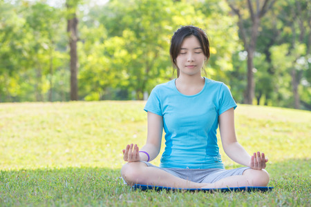 thai yoga: Asian girl making yoga call Easy Pose in park Stock Photo