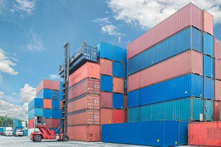 container box: forklift handling container box loading to truck in import export logistic zone