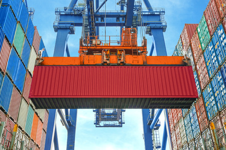 commerce and industry: Shore crane loading containers in freight ship
