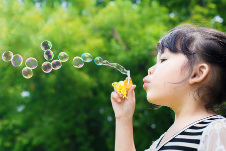 burbujas de jabon: Asia niña soplando pompas de jabón en el parque verde Foto de archivo